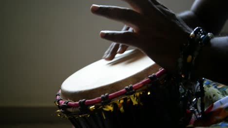 Medium-wide-looking-down-isolated-shot-of-a-man-playing-djembe-drum-alone-in-a-dark-room