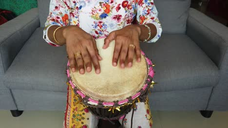 Medium-wide-looking-down-isolated-shot-of-a-woman-playing-djembe-drum