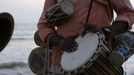 Closeup-of-a-man-playing-African-Djembe-at-a-beach-during-a-beautiful-evening-with-the-sea-in-the-background