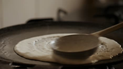 Closeup-slow-motion-view-of-steaming-hot-Dosa-on-a-cast-iron-pan-Dosa-is-the-Indian-version-of-pancake-made-with-rice-flour-dough
