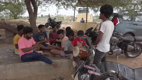 A-group-of-young-boys-singing-country-songs-and-playing-drums-under-a-tree