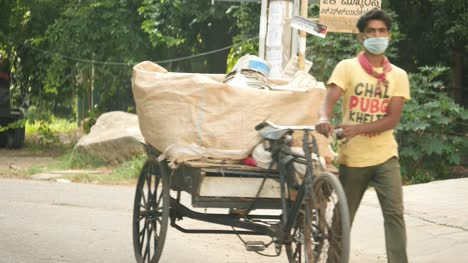 Bengaluru-Karnataka-India-May-15-2020-A-poor-garbage-collector-wearing-mask-and-collecting-garbage-on-a-tricycle-during-covid19-Pandemic-