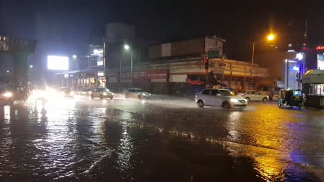 Vehicles-passing-through-MG-road-junction-during-heavy-rain-and-flooding