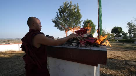 Kollegal-Karnataka-/-India---March-14-2020:-A-young-monk-wearing-a-traditional-Tibetan-Buddhist-robe-performing-a-ritual-with-fire-on-a-platform