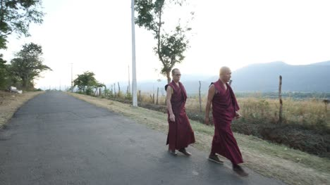 Kollegal-Karnataka-/-India---March-14-2020:-Wide-angle-panning-shot-of-two-monks-walking-on-an-empty-road-with-beautiful-mountains-in-the-background-during-evening