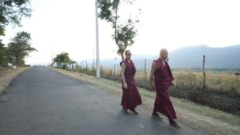 Kollegal-Karnataka-/-India---14-De-Marzo-De-2020:-Toma-Panorámica-De-Gran-Angular-De-Dos-Monjes-Caminando-En-Una-Carretera-Vacía-Con-Hermosas-Montañas-En-El-Fondo-Durante-La-Noche