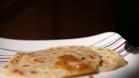 Closeup-dolly-out-dramatic-slow-motion-shot-of-parotta-on-a-plate-with-chicken-curry-being-poured-over-slowly-coming-into-focus