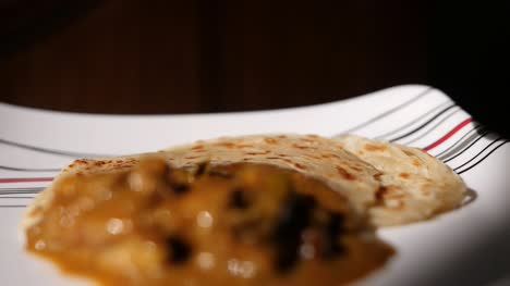 Closeup-dolly-out-dramatic-slow-motion-shot-of-parotta-and-chicken-curry-on-a-plate-with-a-boiled-egg-being-served-slowly-coming-into-focus-