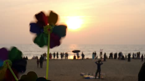 Closeup-of-a-toy-pin-wheel-rotating-in-the-wind-during-a-beautiful-sunset-at-a-beach