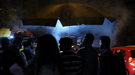 Bengaluru-Karnataka-India-January-25-2020-Medium-shot-of-people-waiting-under-an-umbrella-at-a-street-side-barbecue-shop-with-heavy-smoke-during-night-time