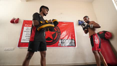 Bengaluru-Karnataka-India-February-13-2020-Looking-up-shot-of-a-professional-mixed-martial-arts-fighter-doing-round-house-spinning-back-kick-and-another-fighter-holding-the-pads