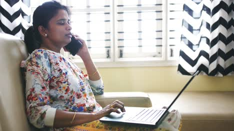 Closeup-of-an-Indian-business-woman-working-from-home-sitting-on-a-sofa-and-talking-on-phone-due-to-the-covid19-coronavirus-lockdown-
