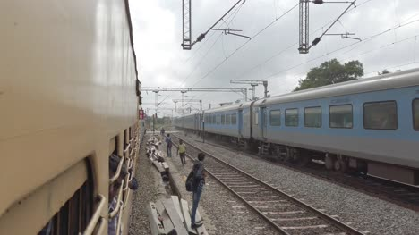 Vaniyambadi-Tamilnadu-India-December-14-2019-People-jumping-from-an-electric-train-and-dangerously-crossing-the-tracks-while-another-train-passes-at-high-speed-in-the-opposite-side