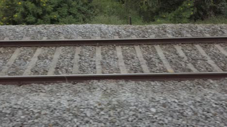 Closeup-of-the-railway-tracks-from-a-fast-moving-train-during-daytime