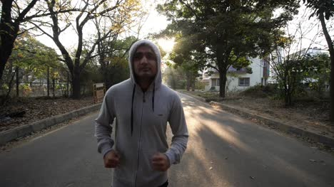 Closeup-of-an-adult-asian-man-wearing-a-hoodie-sweat-shirt-and-jogging-during-dawn