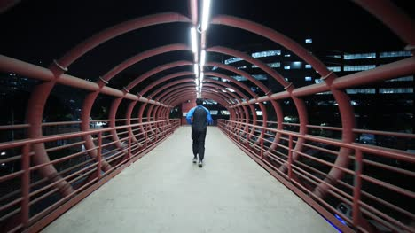 Wide-angle-follow-shot-of-a-man-jogging-on-a-metal-red-colored-skywalk-during-early-morning-hours