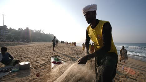 Varkala-Kerala-India-January-01-2020-Medium-shot-of-a-fisherman-preparing-his-fishing-net-during-a-bright-morning