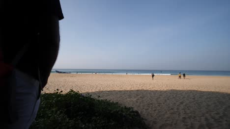 Wide-angle-reveal-shot-of-Varakala-beach-in-Kerala-India-on-a-bright-and-sunny-morning-with-waves-hitting-the-shore