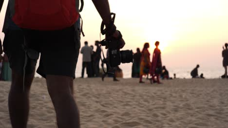 Medium-closeup-of-a-man-wearing-shots-walking-with-a-DSLR-camera-on-a-beach-during-sunset