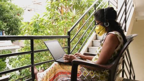 Closeup-of-an-Indian-woman-wearing-safety-mask-and-headset-microphone-working-with-a-laptop-sitting-in-the-balcony-during-the-Covid19-corona-virus-pandemic