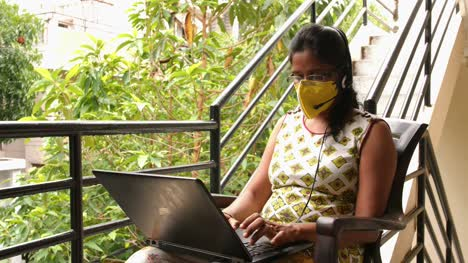 Closeup-of-Indian-woman-wearing-safety-mask-and-headset-microphone-working-with-laptop-sitting-in-the-balcony-during-the-Covid19-corona-virus-pandemic