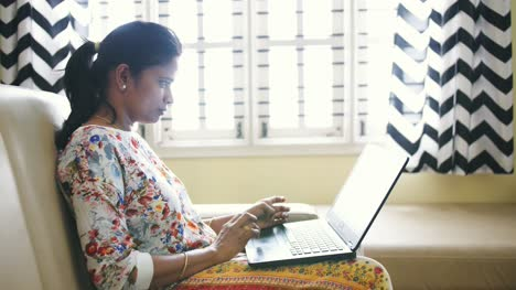Closeup-of-an-Indian-business-woman-working-from-home-sitting-on-a-sofa-due-to-the-covid19-coronavirus-lockdown-