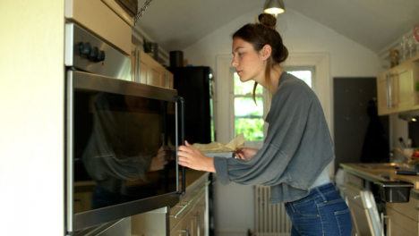 Young-Woman-Placing-Baking-Tin-In-Oven