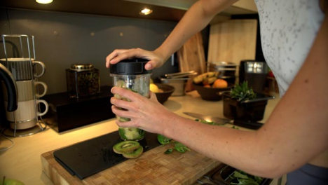 Young-Woman-Placing-Lid-On-Blender-Cup-