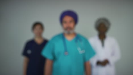 Pull-Focus-of-Three-Happy-Middle-Aged-Doctors-Smiling-Portrait
