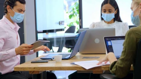 Three-Young-Colleagues-In-Face-Masks-Working-in-Modern-Office