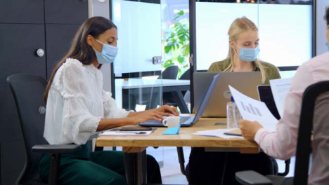 Three-Young-Business-Colleagues-In-Face-Masks-Working-In-Modern-Office