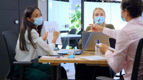 Three-Young-Business-Colleagues-In-Face-Masks-Having-a-Meeting