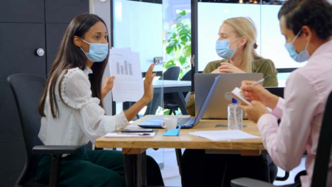 Three-Young-Business-Colleagues-In-Face-Masks-Having-a-Discussion