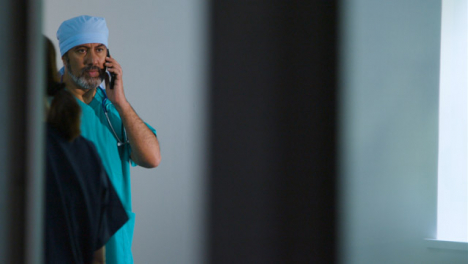 Concerned-Middle-Aged-Surgeon-Finishing-Conversation-On-Mobile-Phone