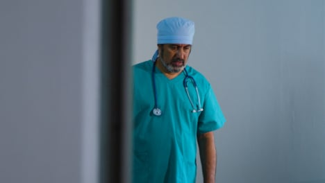 Concerned-Middle-Aged-Surgeon-Having-Conversation-On-Mobile-Phone