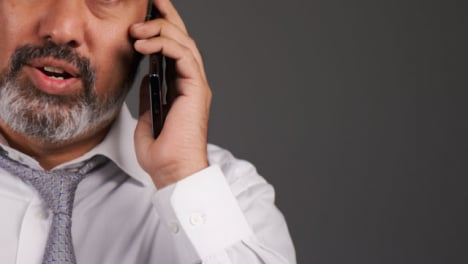 Middle-Aged-Businessman-Having-Heated-Phone-Call-Portrait