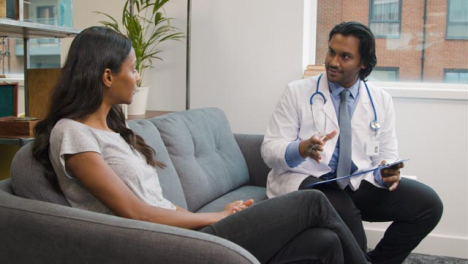 Young-Woman-Having-Relaxed-Chat-with-Doctor