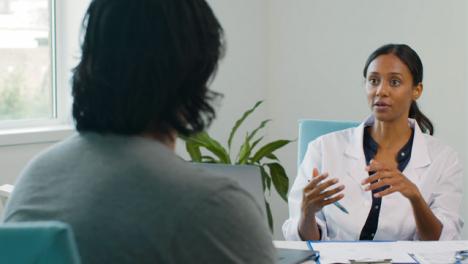Doctora-Se-Sienta-En-Una-Silla-Hablando-Con-El-Paciente