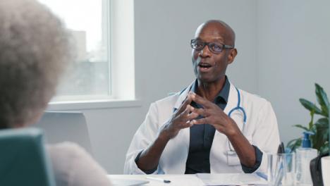 Positiver-Arzt-Mittleren-Alters-Spricht-Mit-Seinem-Patienten