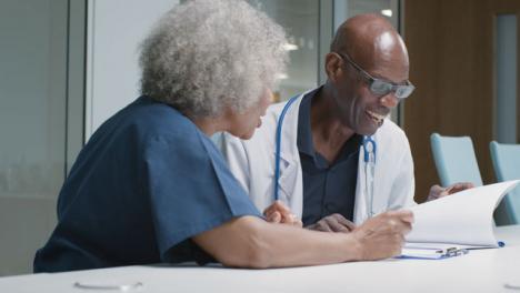 Two-Doctors-Having-Work-Meeting-In-Office-Space