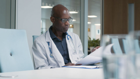 Middle-Aged-Doctor-Goes-Over-Notes-In-Office-Space