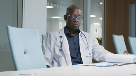 Middle-Aged-Doctor-Goes-Over-Some-Notes-In-Office-Space