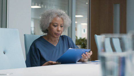 Female-Middle-Aged-Doctor-Looking-at-Notes-In-Office-Space