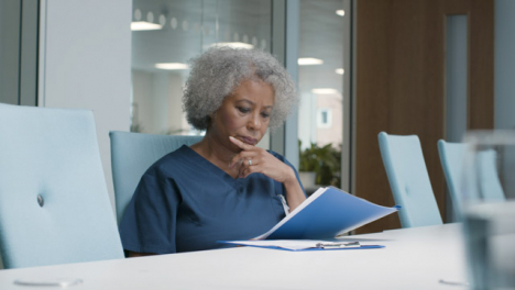 Female-Middle-Aged-Doctor-Going-Over-Notes-In-Office-Space