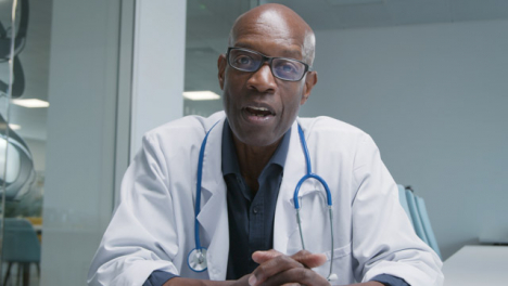 Middle-Aged-Doctor-Leading-Video-Call-Briefing-