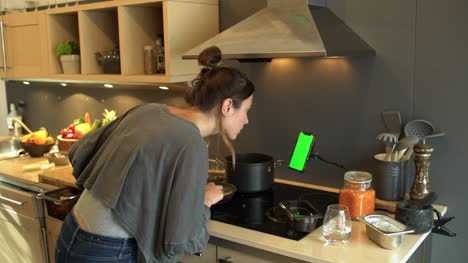 Young-Woman-Cooking-Whilst-Looking-at-Phone-Green-Screen