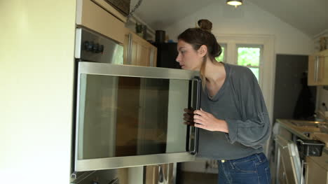 Young-Woman-Places-Baking-Tin-In-Oven