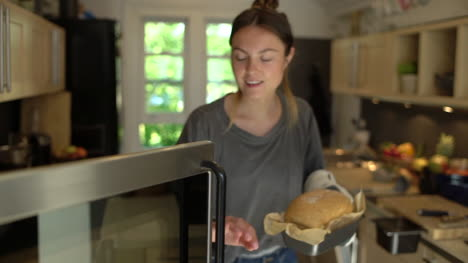 Young-Woman-Taking-Freshly-Baked-Bread-Out-of-Oven