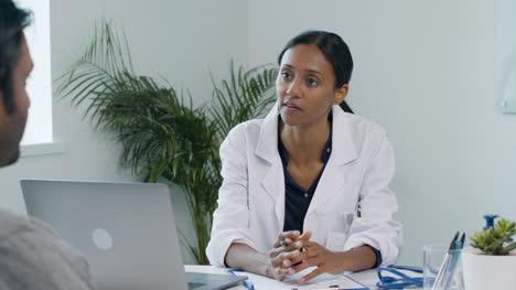 Joven-Médico-Con-Portapapeles-Mientras-Habla-Con-El-Paciente