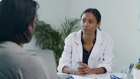 Joven-Médico-Utiliza-El-Portapapeles-Mientras-Habla-Con-El-Paciente